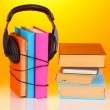 Headphones on books on orange background — Stok fotoğraf