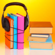 Headphones on books on orange background — 图库照片