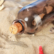 Stock Photo: Glass bottle with note inside on sand