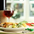 Roast chicken cutlet with boiled potatoes and cucumbers, glass of wine on g — Stock Photo #12569301