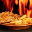 Roast chicken cutlet with french fries, on fire background — Stock Photo