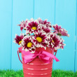 Royalty-Free Stock Photo: Beautiful bouquet of chrysanthemums in a bright colorful bucket on blue fen