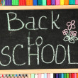 The words 'Back to School' written in chalk on the small school desk with v — Stock Photo #12569425