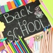 The words 'Back to School' written in chalk on the small school desk with v — Stock Photo #12569442