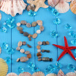 The word sea and decor of seashells close-up on blue wooden table - Stock Photo
