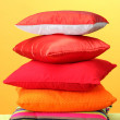 Colorful pillows on yellow background — Stock Photo #12569704
