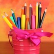 Colorful pencils and felt-tip pens in pink pail on color background — Stockfoto