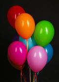 Colorful balloons on black background close-up — Stock Photo