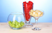 Color candies in glasses on wooden table on blue background — Stock Photo