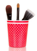 Cosmetic brushes in cup isolated on white — Stock Photo