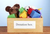 Caja de la donación con juguetes de los niños en primer plano de fondo azul — Foto de Stock