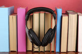 Auriculares en libros sobre tabla de madera sobre fondo rosa — Foto de Stock