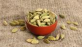 Zelený kardamon v keramickém misku na plátně pozadí detail — Stock fotografie