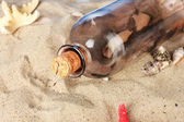 Glass bottle with note inside on sand — Stock Photo