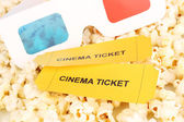 Cinema tickets and glasses on popcorn background — Stock Photo