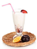 Delicious milk shake with fruit on wicker cradle isolated on white — Stock Photo