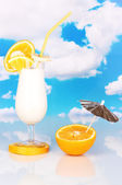 Delicious milk shake with fruit on table on sky background — Stock Photo