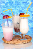 Delicious milk shakes with fruit on wicker cradle on blue sea background — Stock Photo