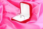 обручальные кольца в красном поле на фоне розовой ткани — Стоковое фото