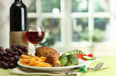 Roast chicken with french fries and cucumbers, glass of wine on green table — Stock Photo
