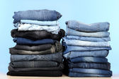 Many jeans stacked in a piles on blue background — Stock Photo