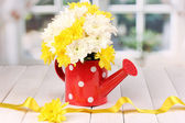 Red watering can of peas with flowers on white wooden table on window back — Stock Photo