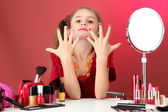 Little girl in her mother's dress, is trying painting her nails — Stock Photo