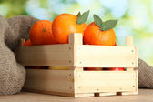 Ripe tasty tangerines with leaves in wooden box on table on green backgroun — Stock Photo