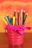 Colorful pencils and felt-tip pens in pink pail on color background — Stock Photo