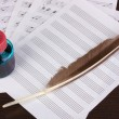Musical notes and feather on wooden table — Stock Photo #12574907