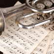 Musical notes and trumpet on wooden table - Stockfoto
