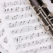 Musical notes and clarinet on wooden table - Stockfoto
