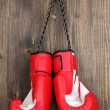 Red boxing gloves hanging on wooden background — Stock Photo #12575109