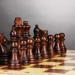 Chess board with chess pieces on grey background — Foto Stock