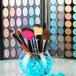 Make-up brushes in a bowl with stones on palette of shadows background — Stock Photo