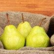 Ripe pears in sack on wooden background close-up — Stock Photo #12575753