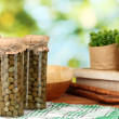Glass jars with tinned capers on green background — Stock Photo