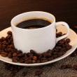 Cup of coffee close-up on wooden table on brown background — Stock Photo