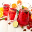 Stock Photo: Sangria in jar and glasses with fruits, on white wooden table