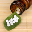 Medicine bottle with tablets on green leaf on bamboo mat - Foto Stock