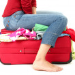 The girl is trying to close suitcase crammed on white background - Stock Photo