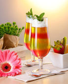 Fruit jelly in glasses and fruits on table in cafe — Stock Photo