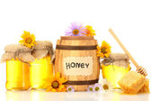 Sweet honey in jars and barrel with honeycomb, wooden drizzler and flowers — Stock Photo