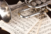 Musical notes and trumpet on wooden table — Stock Photo