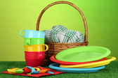 Bright plastic disposable tableware and picnic basket on the lawn on colorf — Stock Photo