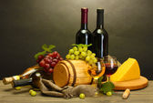 Barrel, bottles and glasses of wine, cheese and ripe grapes on wooden table — Stock Photo