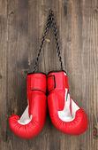 Rote boxhandschuhe hängen hölzerne hintergrund — Stockfoto