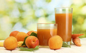 Glasses of carrot and apricot juice on white wooden table on green backgro — Stock Photo