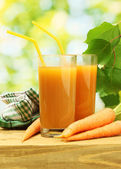 Glasses of carrot juice and fresh carrots on wooden table on green backgrou — Stock Photo