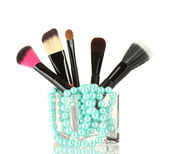 Make-up brushes in glass cup with pearl necklace isolated on white — Stock Photo